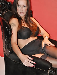 Sultry Jane is dressed all in black and sitting on her..