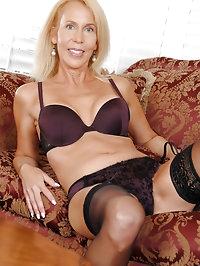 Sensual milf stunner fondles her juicy tits on the sofa..